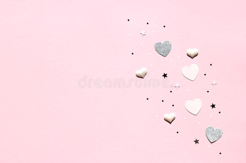 Valentine`s Day background. Gold and silver hearts and black stars on pastel pink background. Valentines day concept. Top view,. Valentine`s Day background royalty free stock image