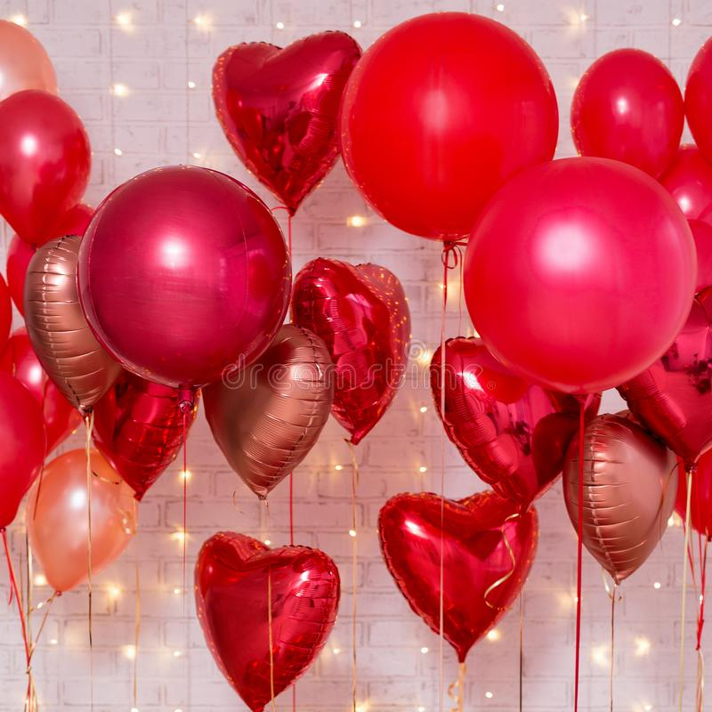 Valentine`s day background - group of red air balloons over brick wall. Valentine`s day background - group of red air balloons over white brick wall stock photo