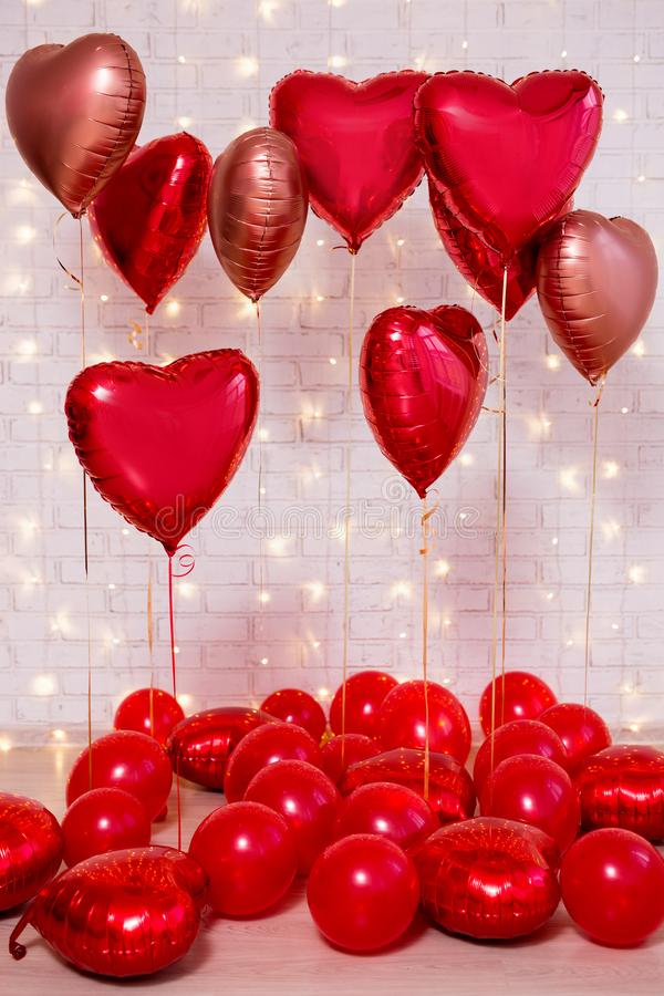 Valentine`s day background - group of red balloons over brick wall. Valentine`s day background - group of red balloons over white brick wall stock images