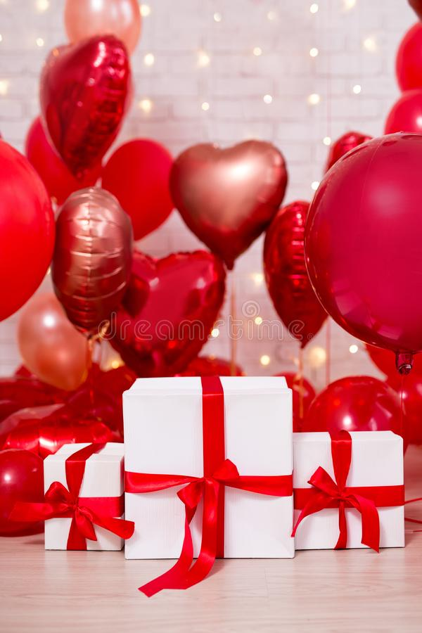 Valentine`s day background - group of red balloons and white gift boxes. Valentine`s day background - group of red air balloons and white gift boxes royalty free stock photos