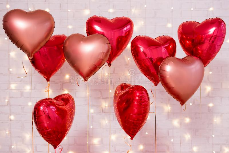 Valentine`s day background - group of red heart shaped balloons over brick wall. Valentine`s day background - group of red heart shaped balloons over white brick stock photo