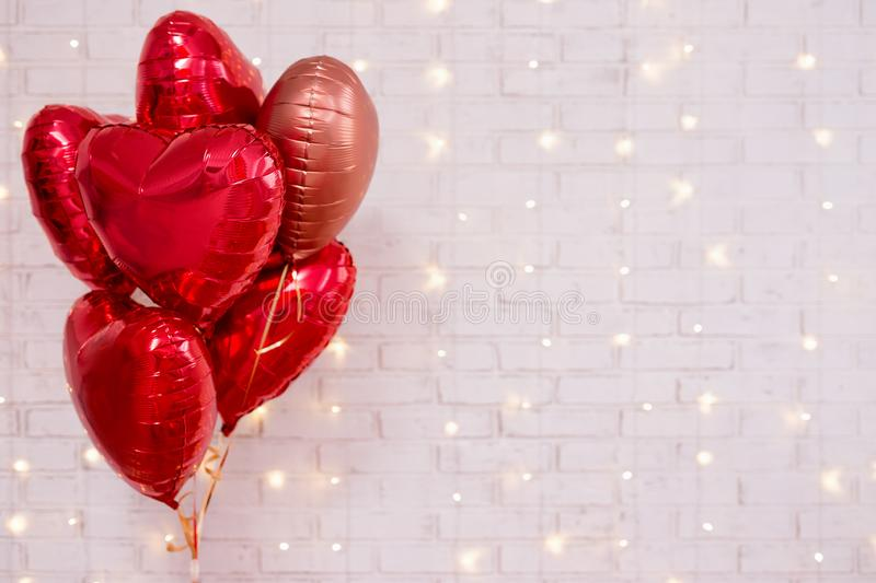 Valentine`s day background - group of red heart shaped balloons over white wall with lights. Valentine`s day background - group of red heart shaped balloons over royalty free stock photo