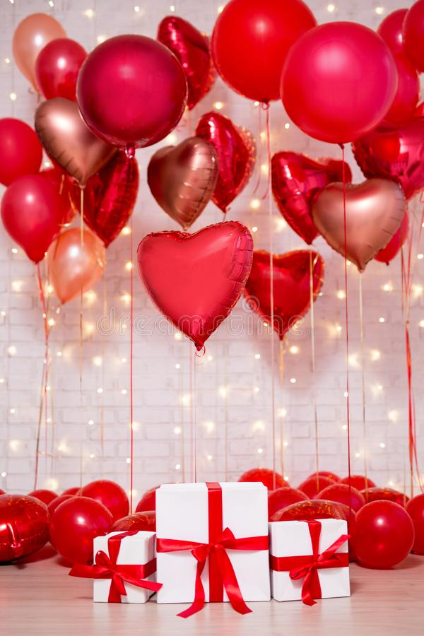 Valentine`s day background - group of red heart shaped foil balloons and gift boxes. Valentine`s day background - group of red heart shaped foil balloons and stock image