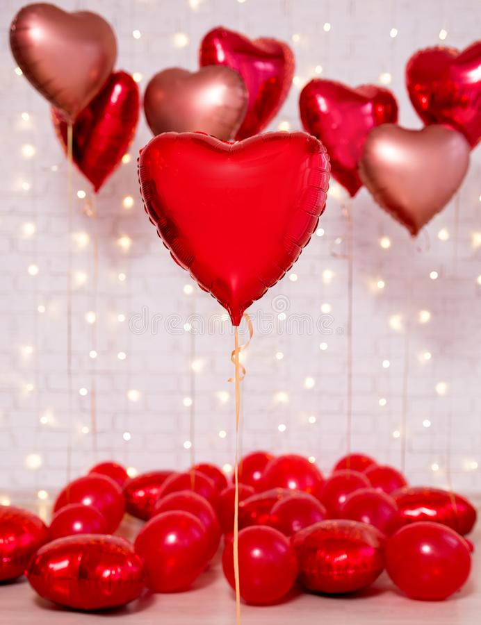 Valentine`s day background - group of red heart shaped foil balloons over brick wall. Valentine`s day background - group of red heart shaped foil balloons over royalty free stock image