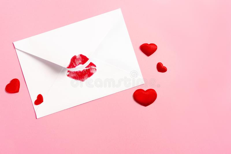 Valentine`s day background. Envelope with red lipstick kiss and hearts on pink. stock image