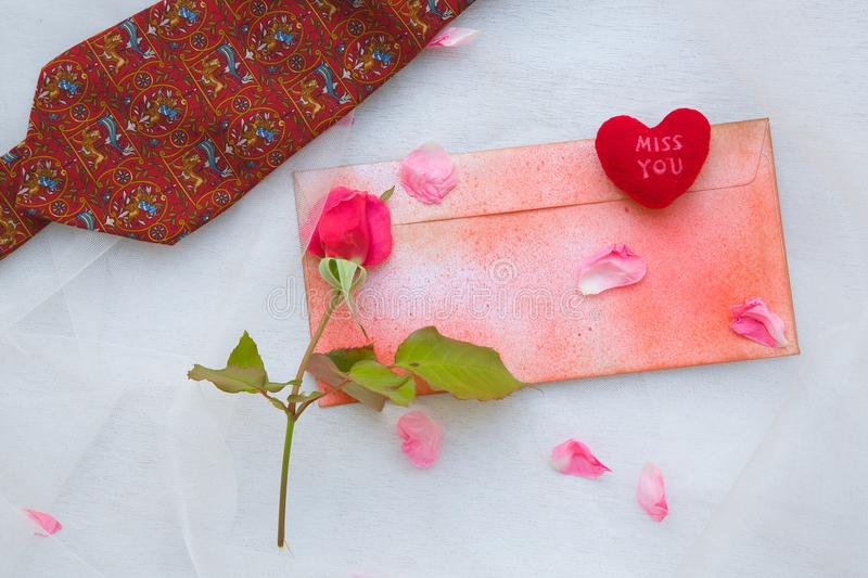 Valentine's Day background. Man's tie,rose,rose petals,plush heart Miss you,a red envelope on a transparent fabric royalty free stock photography
