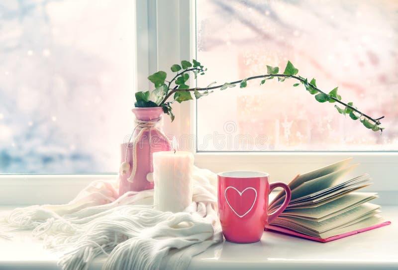 Valentine`s day background,mug on window still.Comfort winter life style stock photo