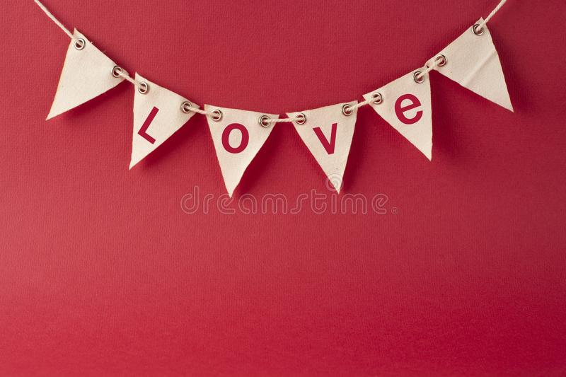Valentine's day background. Party decorative garland with Love words, inscription. Red background for design or copy space. Party decorative garland with stock images