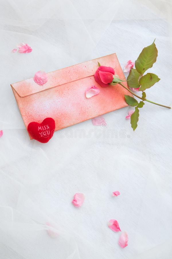 Valentine's Day background. Pink rose, pink rose petals,plush heart Miss you,red envelope on a transparent fabric. Free space for a text stock photos