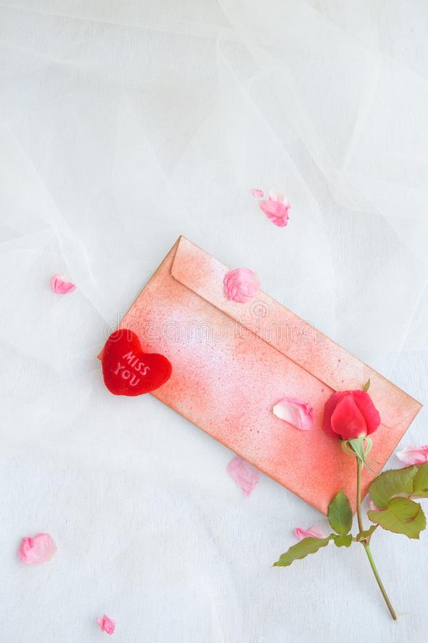 Valentine's Day background. Pink rose, pink rose petals,plush heart Miss you,a red envelope on a transparent fabric. Free space for a text royalty free stock photography