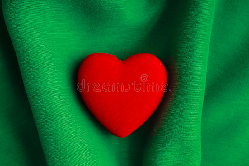 Valentine's day background. Red heart on green folds cloth royalty free stock image