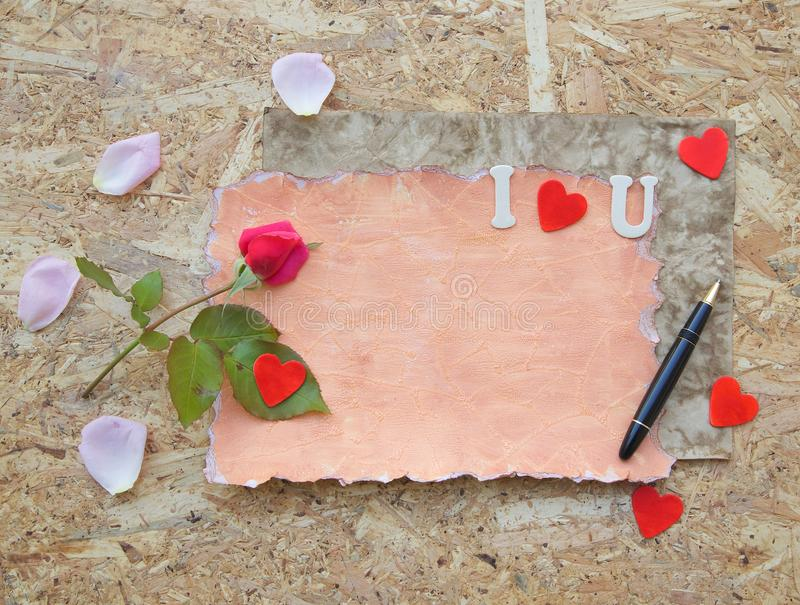 Valentine's Day background. Red rose, pink rose petals,wooden red hearts, black vintage pen on a wooden surface. Free space for a text royalty free stock images