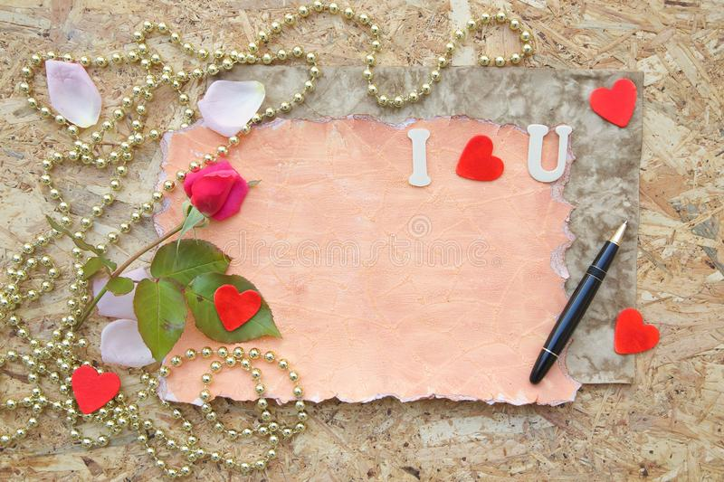 Valentine's Day background. Red rose, pink rose petals,wooden red hearts, black vintage pen on a wooden surface. Free space for a text royalty free stock photo