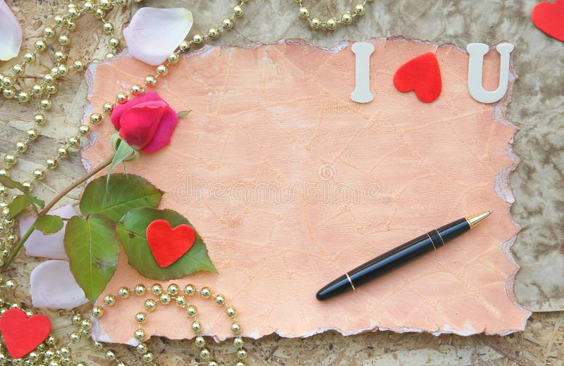 Valentine's Day background. Red rose, pink rose petals,wooden red hearts, black vintage pen on a wooden surface. Free space for a text stock image