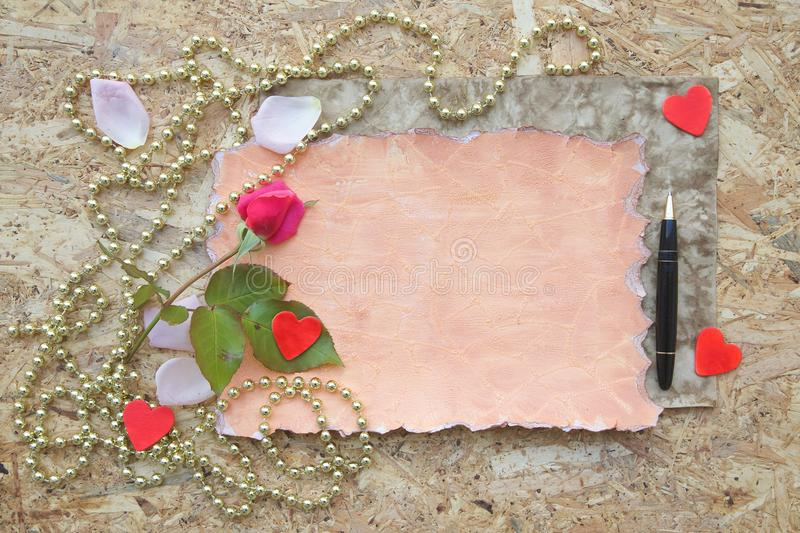 Valentine's Day background. Red rose, pink rose petals,wooden red hearts, black vintage pen on a wooden surface. Free space for a text stock images