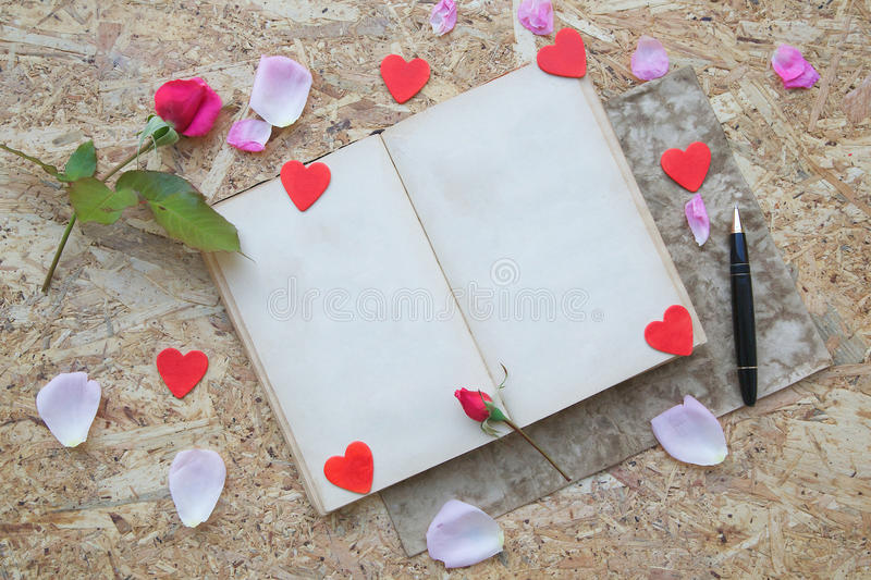 Valentine's Day background. Red rose, pink rose petals,wooden red hearts, old book with free space for a text ,black vintage pen on a wooden surface royalty free stock photography