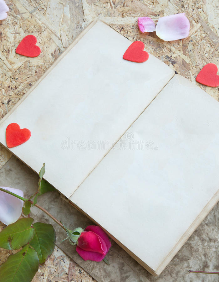 Valentine's Day background. Red rose, pink rose petals,wooden red hearts, old book with free space for a text ,black vintage pen on a wooden surface royalty free stock photos