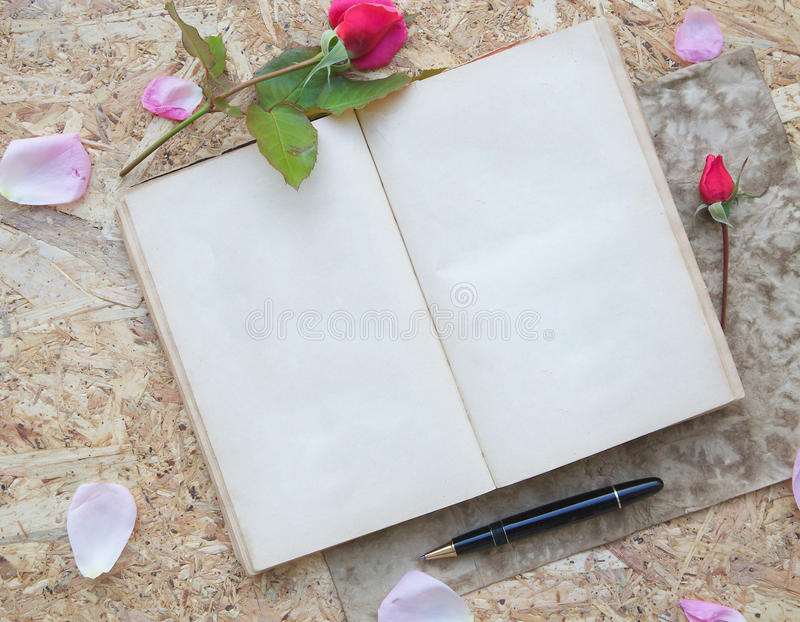 Valentine's Day background. Red rose, pink rose petals,wooden red hearts, old book with free space for a text ,black vintage pen on a wooden surface royalty free stock image