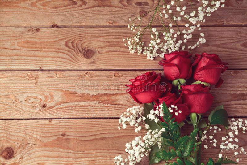 Valentine's day background with red roses on wooden table. View from above stock images