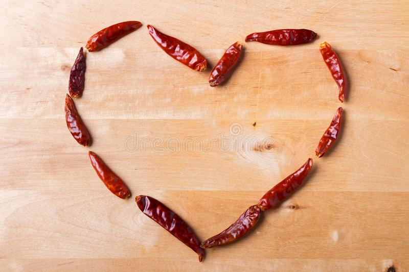 Valentine`s day background. The sign of the Heart is laid out of red hot chili peppers on a wooden background. Love royalty free stock image