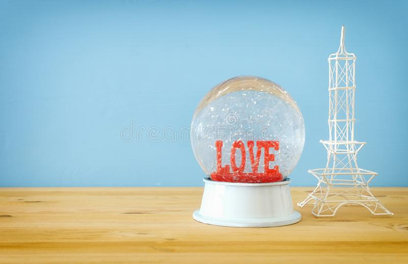 Valentine`s day background. Water globe with word LOVE. And glitter next eiffel tower, over the wooden table and blue bakground royalty free stock photos