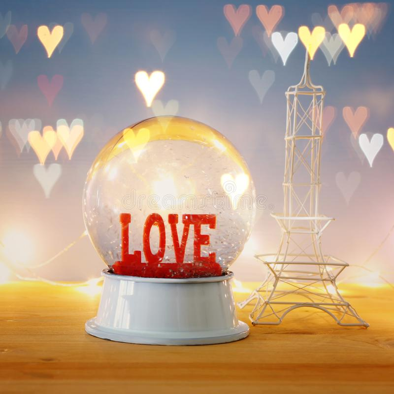 Valentine`s day background. Water globe with word LOVE. And glitter next eiffel tower, over the wooden table and blue bakground. Hearts overlay stock photography