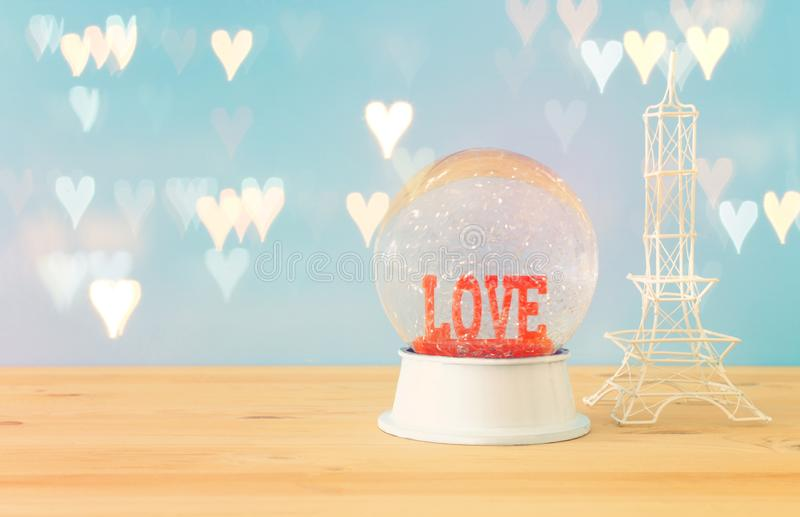Valentine`s day background. Water globe with word LOVE. And glitter next eiffel tower, over the wooden table and blue bakground. Hearts overlay royalty free stock photos