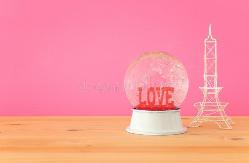 Valentine& x27;s day background. Water globe with word LOVE. And glitter next eiffel tower, over the wooden table and pink bakground stock photos