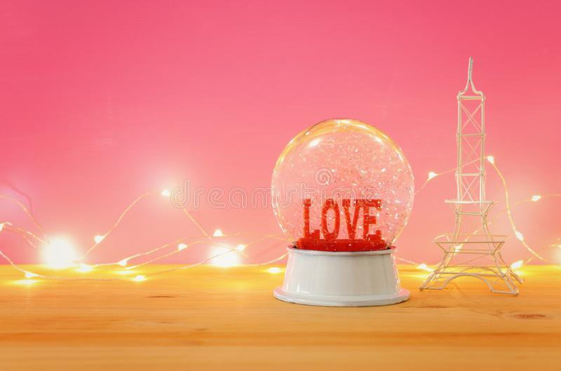 Valentine's day background. Water globe with word LOVE. And glitter next eiffel tower, over the wooden table and pink bakground stock photos