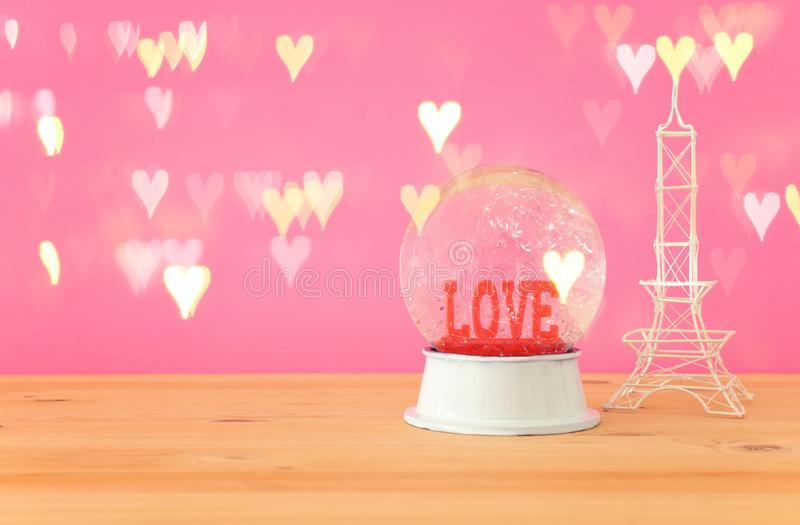 Valentine`s day background. Water globe with word LOVE. And glitter next eiffel tower, over the wooden table and pink bakground. Hearts overlay stock photo