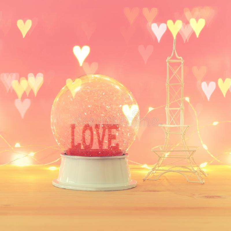 Valentine`s day background. Water globe with word LOVE. And glitter next eiffel tower, over the wooden table and pink bakground. Hearts overlay royalty free stock photo
