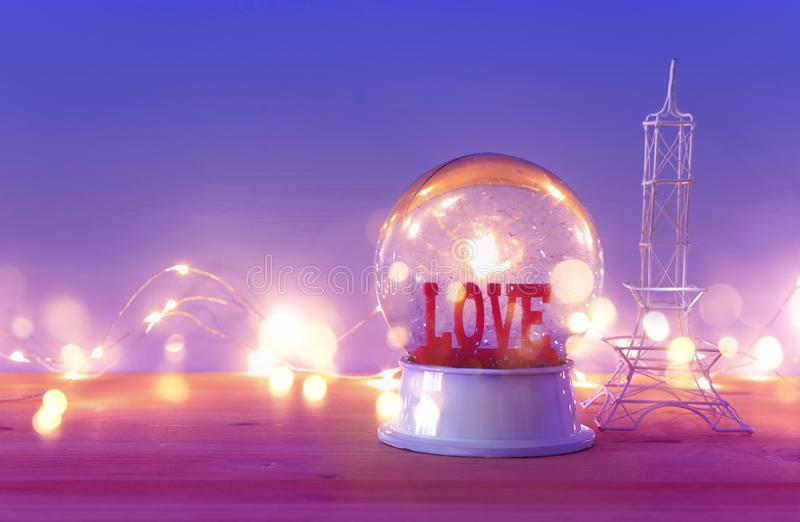 Valentine`s day background. Water globe with word LOVE. And glitter next eiffel tower, over the wooden table and purple bakground stock photos