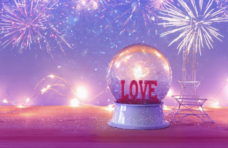 Valentine`s day background. Water globe with word LOVE. And glitter next eiffel tower, over the wooden table and purple bakground. Fireworks overlay royalty free stock image