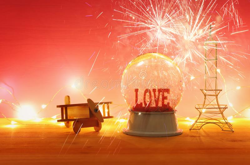 Valentine's day background. Water globe with word LOVE and glitter. Next eiffel tower, wooden toy plane, over the table and pink bakground. Fireworks stock image