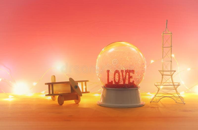 Valentine`s day background. Water globe with word LOVE. And glitter next eiffel tower, wooden toy plane, over the table and pink bakground stock images