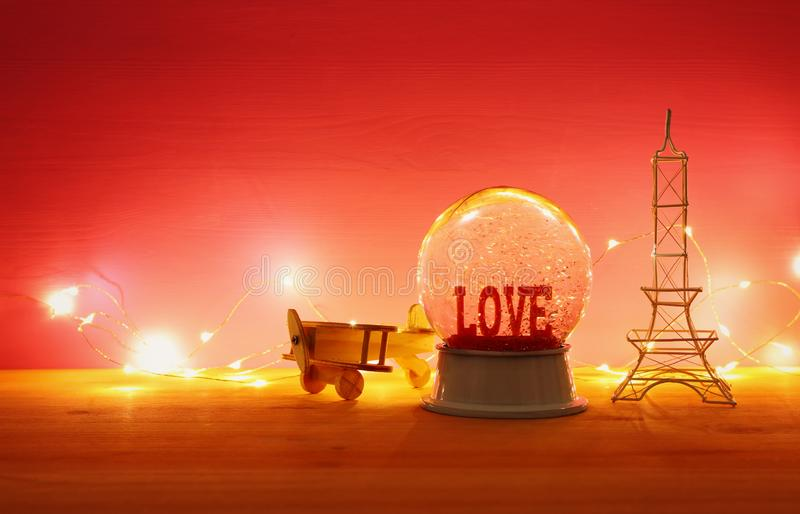 Valentine's day background. Water globe with word LOVE. And glitter next eiffel tower, wooden toy plane, over the table and red bakground royalty free stock photos