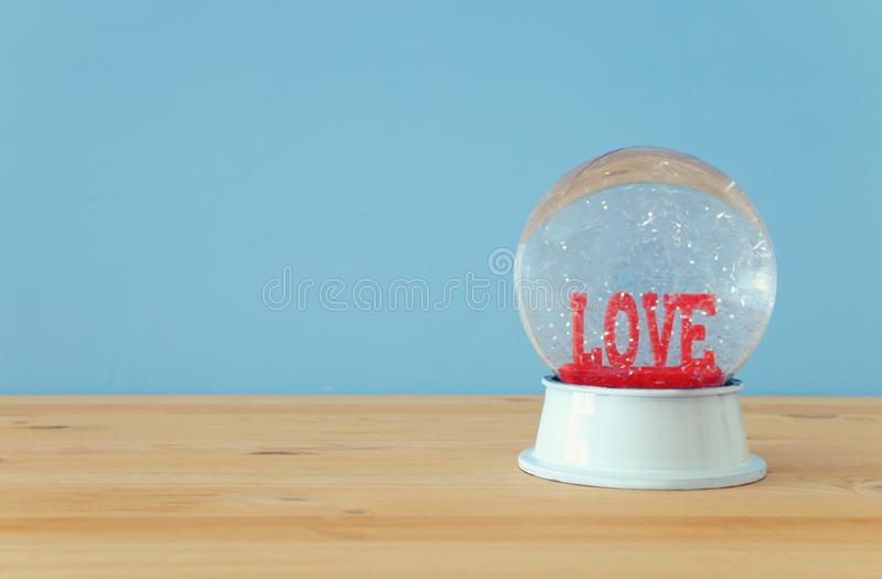 Valentine's day background. Water globe with word LOVE and glitter over the wooden table and blue bakground. Valentine's day background. Water globe stock photography