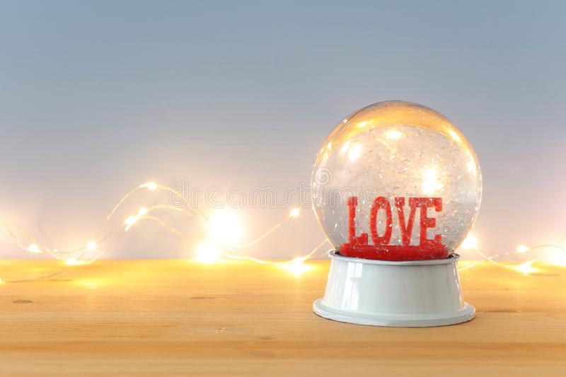 Valentine's day background. Water globe with word LOVE and glitter over the wooden table and blue bakground. Valentine's day background. Water globe stock image