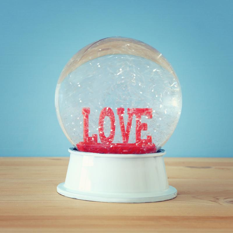 Valentine& x27;s day background. Water globe with word LOVE and glitter over the wooden table and blue bakground. Valentine& x27;s day background. Water globe stock images