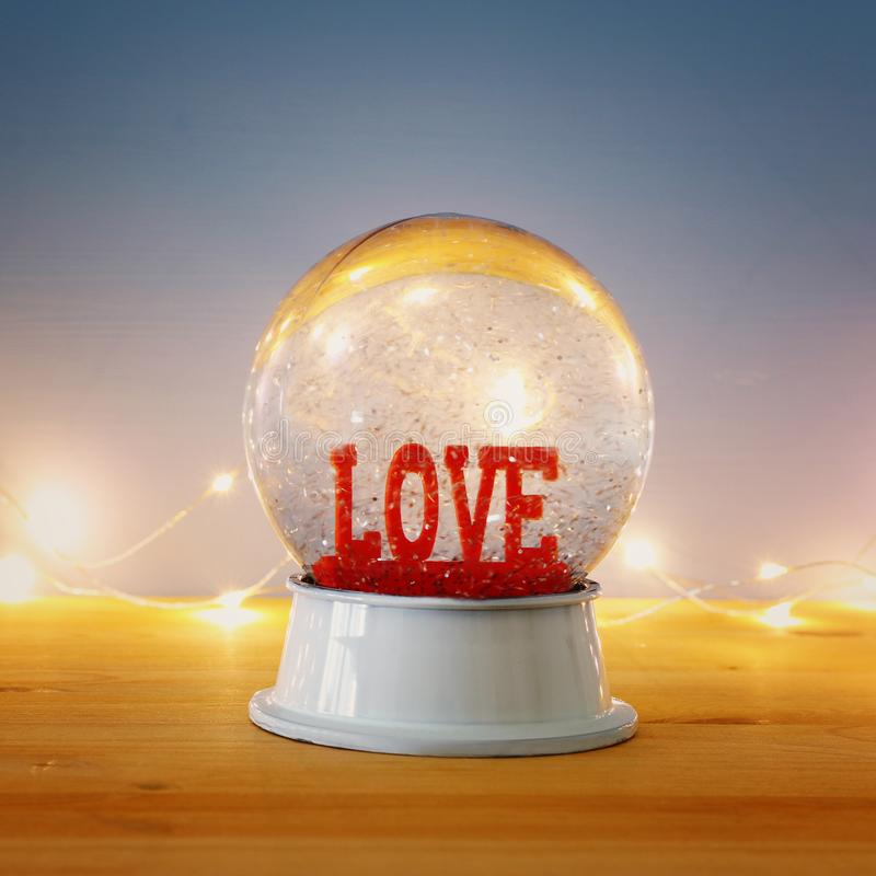 Valentine's day background. Water globe with word LOVE and glitter over the wooden table and blue bakground. Valentine's day background. Water globe royalty free stock photography