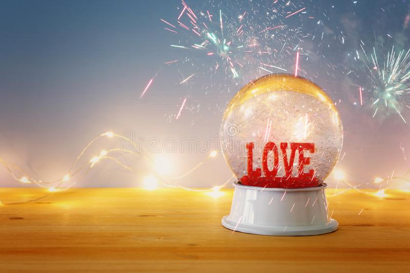 Valentine`s day background. Water globe with word LOVE. And glitter over the wooden table and blue bakground. Fireworks overlay royalty free stock photo