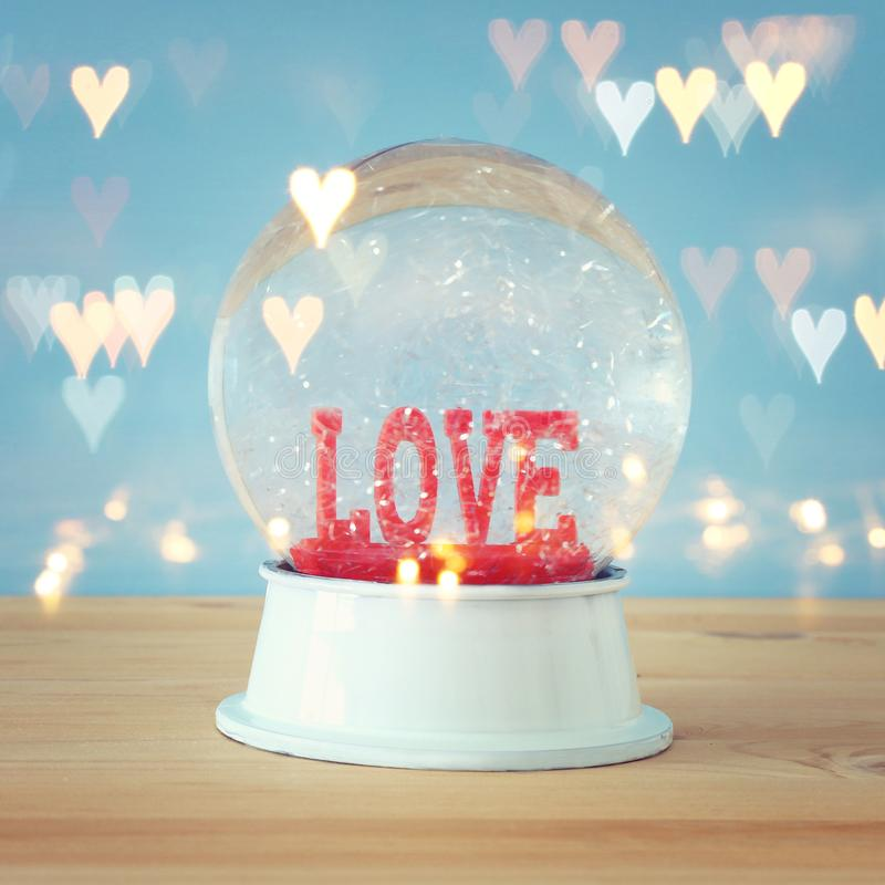 Valentine's day background. Water globe with word LOVE and glitter over the wooden table and blue bakground. Hearts overlay. Valentine's day royalty free stock photography