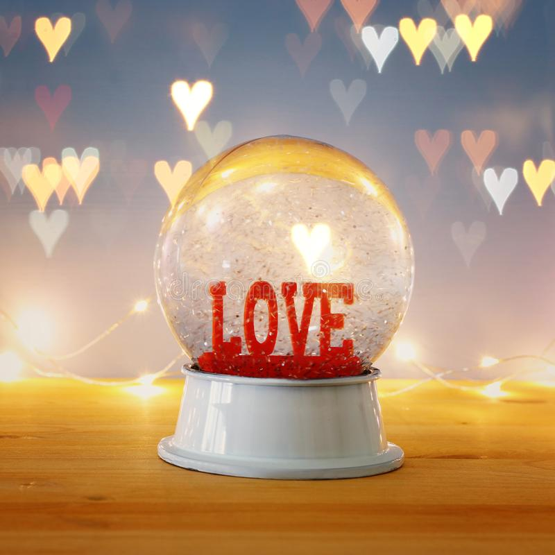 Valentine's day background. Water globe with word LOVE and glitter over the wooden table and blue bakground. Hearts overlay. Valentine's day stock photo
