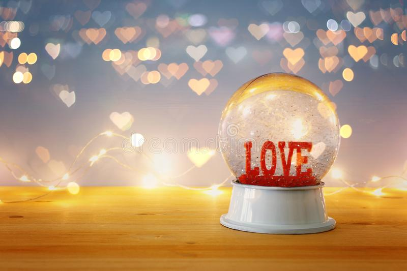 Valentine's day background. Water globe with word LOVE and glitter over the wooden table and blue bakground. Hearts overlay. Valentine's day stock image