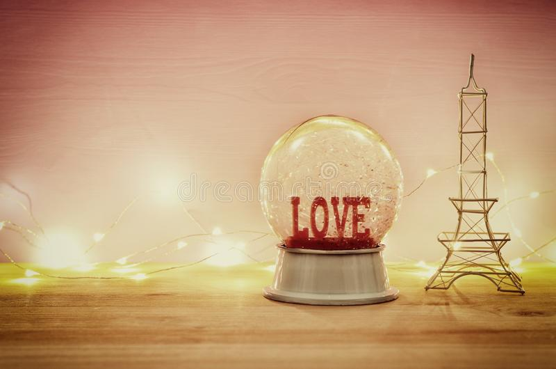 Valentine's day background. Water globe with word LOVE and glitter over the wooden table and pink bakground. Valentine's day background. Water globe stock photography