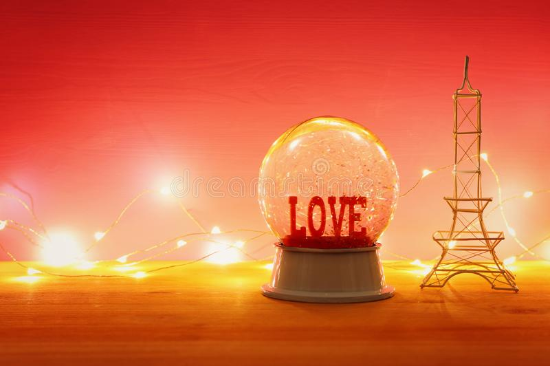 Valentine's day background. Water globe with word LOVE and glitter over the wooden table and pink bakground. Valentine's day background. Water globe stock photo
