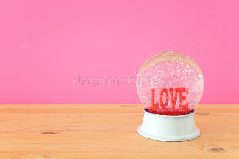 Valentine's day background. Water globe with word LOVE and glitter over the wooden table and pink bakground. Valentine's day background. Water globe royalty free stock photos