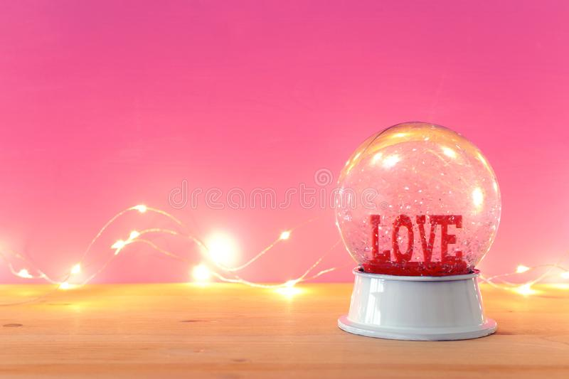 Valentine's day background. Water globe with word LOVE and glitter over the wooden table and pink bakground. Valentine's day background. Water globe royalty free stock image