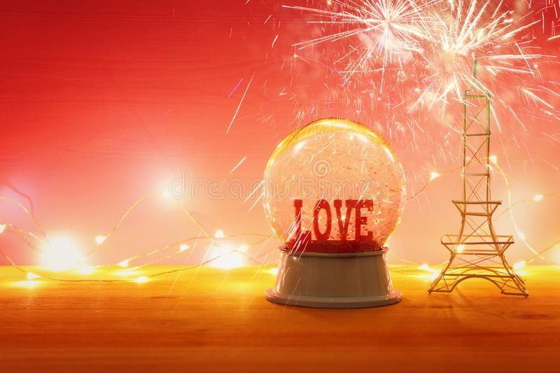 Valentine's day background. Water globe with word LOVE and glitter. Over the wooden table and pink bakground. Fireworks overlay royalty free stock image