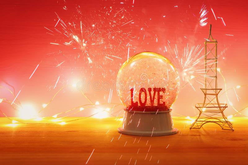 Valentine`s day background. Water globe with word LOVE. And glitter over the wooden table and pink bakground. Fireworks overlay royalty free stock image